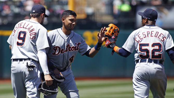 Detroit Tigers' Dixon Machado, center, celebrates with teammates Nick Castellanos, left, and Yoenis Cespedes, after making his first major league hit, during the sixth inning of a baseball game against the Oakland Athletics, Wednesday, May 27, 2015, in Oakland, Calif. (AP Photo/George Nikitin)