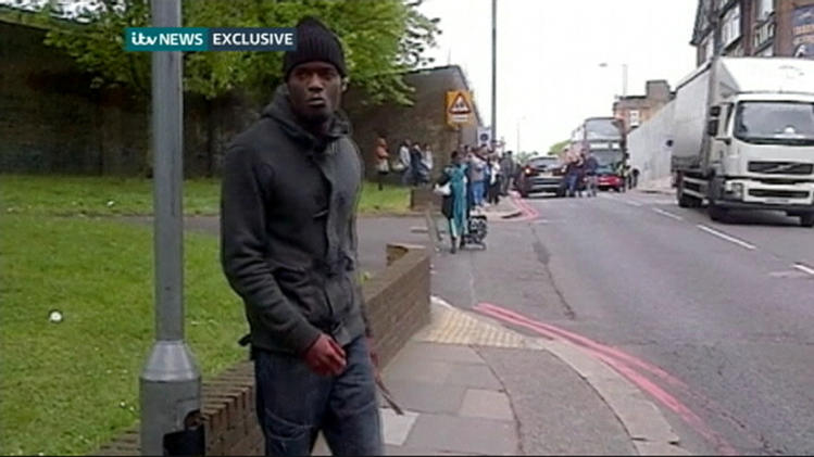 Still image of Adebolajo showing a bloodied hand and knives following the murder of soldier Rigby in Woolwich