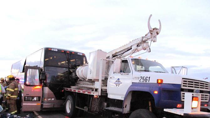 In a photo provided by the Utah Highway Patrol emergency workers respond at the scene of an accident on I-80 in Utah, after a tour bus ran into a utility truck carrying an auger Monday Oct. 28, 2013. The Utah Highway Patrol said driver was impaled and killed by the drilling device and three passengers are in critical condition. (AP Photo/ Utah Highway Patrol)