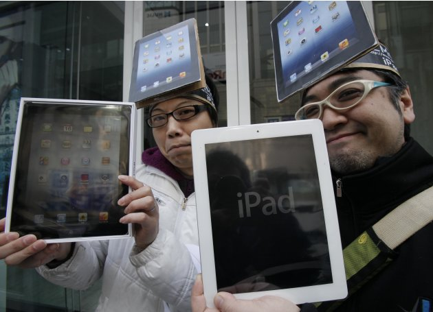 Japanese Ryota Musha, 41, right, and Hisanori Kogure, 31, show off new iPad tablet computers they purchased, in Tokyo Friday, March 16, 2012. Sales of the third version of Apple's iPad began Frida