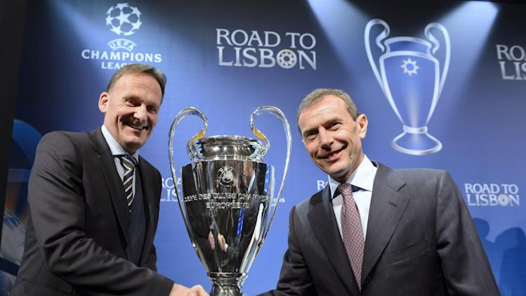 to Real Madrid's Emilio Butragueno next to the trophy after the draw