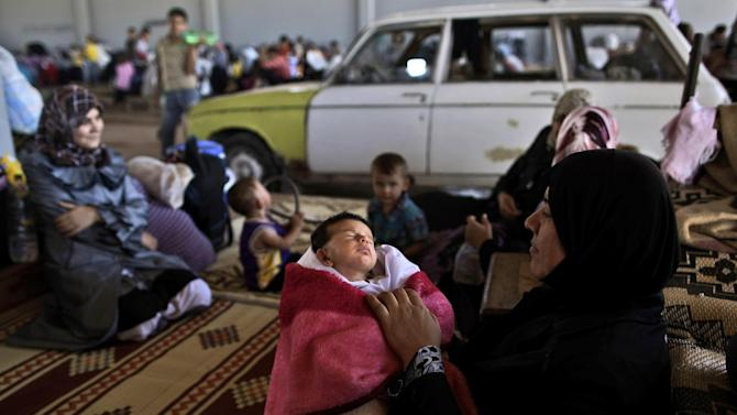A Syrian woman, who fled her home due to fighting between the Syrian army and the rebels, holds her child, while she and others take refuge at the Bab Al-Salameh border crossing in hopes of entering one of the refugee camps in Turkey, near the Syrian town of Azaz, Thursday, Aug. 23, 2012. Thousands of Syrians who have been displaced by the country's civil are struggling to find safe shelter while shelling and airstrikes by government forces continue. (AP Photo/Muhammed Muheisen)
