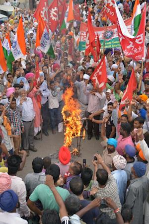 Leftist activists shout slogans as they burn an effigy …