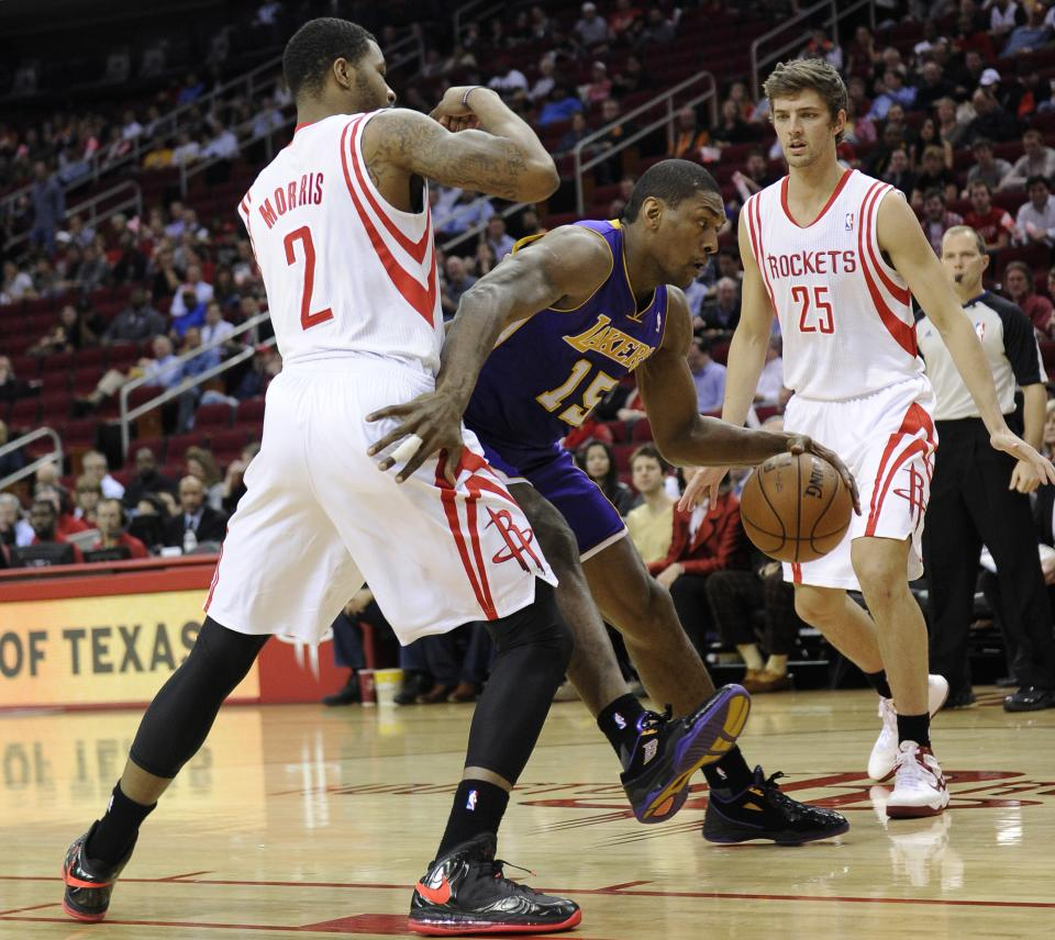 Los Angeles Lakers' Metta World Peace (15) tries to get past Houston Rockets' Marcus Morris (2) as Chandler Parsons (25) looks on in the first half of an NBA basketball game Tuesday, Jan. 8, 2013, in Houston. (AP Photo/Pat Sullivan)