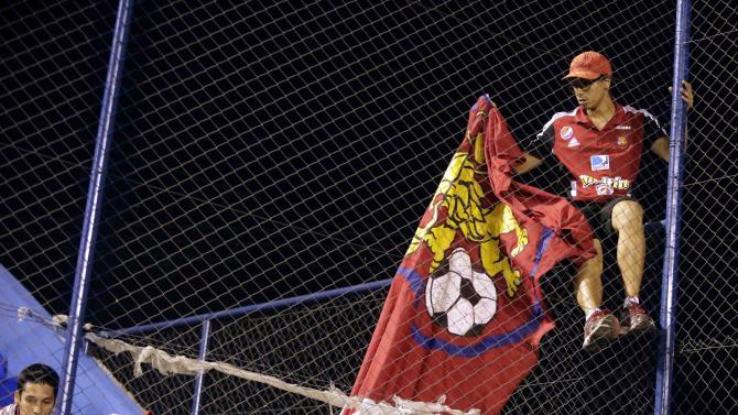 Fans of Venezuela's Caracas hang up their team's flag before their Copa Sudamericana soccer match against Paraguay's Deportivo Capiata, in Capiata