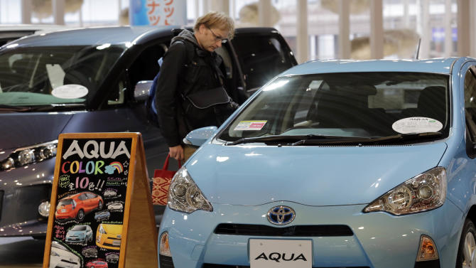 """A man inspects an """"Aqua"""" at a Toyota Motor Corp. showroom in Tokyo Monday, Nov. 5, 2012. Toyota's quarterly profit tripled, driven by a recovery from natural disasters, and the company raised its full-year earnings forecast despite a sales slump in China. (AP Photo/Koji Sasahara)"""