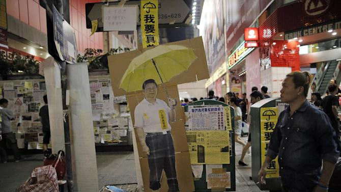 """A cut-out picture of Chinese President Xi Jinping is placed in the occupied area of the Mong Kok district Hong Kong Saturday, Oct. 25, 2014. Pro-democracy protesters in Hong Kong plan to hold a spot referendum Sunday on whether to stay in the streets or accept government offers for more talks and clear their protest camps. A yellow sticker on Xi reads: """"""""I want real universal suffrage."""" (AP Photo/Vincent Yu)"""