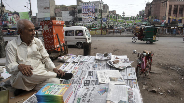 A newspapers vendor sits next to morning newspapers reporting on Pakistan's parliamentary election, at a stall in Lahore, Pakistan on Sunday, May 12, 2013. Former Pakistani Prime Minister Nawaz Sharif declared victory following a historic election marred by violence Saturday, a remarkable comeback for a leader once toppled in a military coup and sent into exile. (AP Photo/K.M. Chaudary)