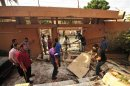 People help clear debris at the scene of a blast at the Egyptian consulate building in Benghazi