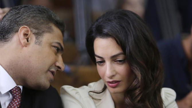 Canadian Al-Jazeera English journalist Mohammed Fahmy, left, talks to human rights lawyer Amal Clooney before his verdict in a courtroom in Tora prison in Cairo, Egypt, Saturday, Aug. 29, 2015. Fahmy is being tried along with Egyptian producer Baher Mohammed on charges accusing them of being part of a terrorist group and airing falsified footage intended to damage national security. An Egyptian court on Saturday sentenced three Al-Jazeera English journalists to three years in prison, the last twist in a long-running trial criticized worldwide by press freedom advocates and human rights activists. (AP Photo/Amr Nabil)