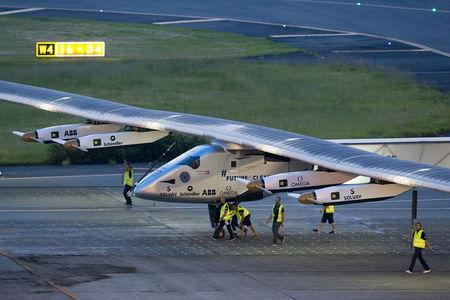 Crew members push solar powered plane Solar Impulse 2 to its parking position at Nagoya airport after changing weather conditions thwarted planned take-off