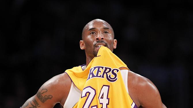 Los Angeles Lakers' Kobe Bryant bites his jersey as a tattoo with the name of his wife, Vanessa, is seen on his arm during the NBA preseason basketball game against the Los Angeles Clippers in Los Angeles on Monday, Dec. 19, 2010. Vanessa Bryant filed for divorce from Kobe last Friday. (AP Photo/Danny Moloshok)