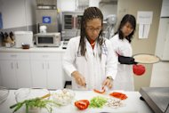 Lockeed Martin research scientist Maya Cooper, left, and Monica Leong, right, prepare a vegan pizza at NASA's Advanced Food Technology Project at Johnson Space Center Tuesday, July 3, 2012, in Houston. NASA is currently planning a mission to Mars, which has gravity, so more options for food preparation, like chopping vegetables, are available as opposed to the dehydrated fare of current space missons. (AP Photo/Michael Stravato)