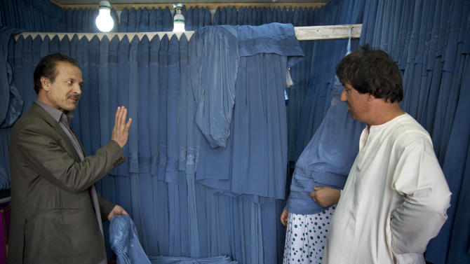 In this Thursday, April 11, 2013 photo, Alim Nazery, left, owner of a burqa store in Kabul's old town market for 27 years, bargains with an Afghan couple about the price of a new burqa in Kabul, Afghanistan. Alim, as well as a wholesale business, remembers selling at least 50 burqas a day when the Taliban were in charge and enforcing their strict morality rules. Now that number has dropped to 20 and most are sold to women who travel from areas outside Kabul to buy from him because of his reputation for quality. (AP Photo/Anja Niedringhaus)