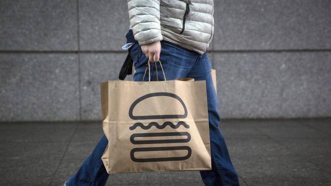 A man carries away bags of Shake Shack in New York
