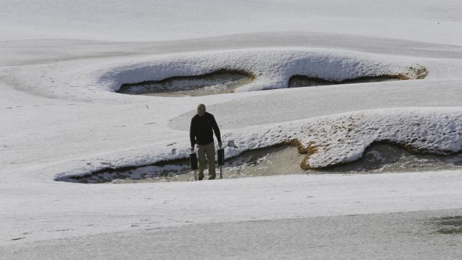 A grounds keeper picks up practice balls out of bunkers on the practice range before play resumes for the first round of the Match Play Championship golf tournament, Thursday, Feb. 21, 2013, in Marana, Ariz.  A snow storm blanketed the course on Wednesday suspending the first round of play and postponing it until late Thursday morning. (AP Photo/Ted S. Warren)