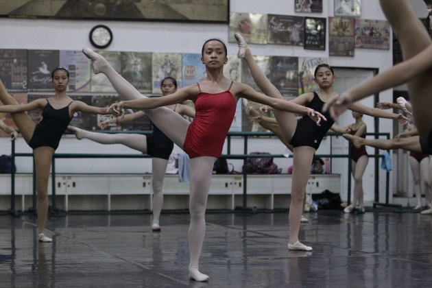 In this photo taken Nov. 25, 2012, Filipino slum dweller Jessa Balote, center, practices with other students during a class at Ballet Manila in the Philippine capital. Balote, who used to tag along wi