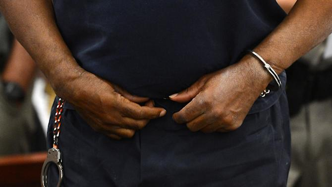 One hand of O.J. Simpson is unshacled as Simpson stands during a break in the second day of  an evidentiary hearing in Clark County District Court, Tuesday, May 14, 2013 in Las Vegas.  The hearing is aimed at proving Simpson's trial lawyer, Yale Galanter,  had conflicted interests and shouldn't have handled Simpson's case. Simpson is serving nine to 33 years in prison for his 2008 conviction in the armed robbery of two sports memorabilia dealers in a Las Vegas hotel room.  Judge Linda Marie Bell let Simpson have one hand unshackled to drink water and take notes.  His left hand was still cuffed to the arm of his chair during the hearing. (AP Photo/Ethan Miller, Pool)