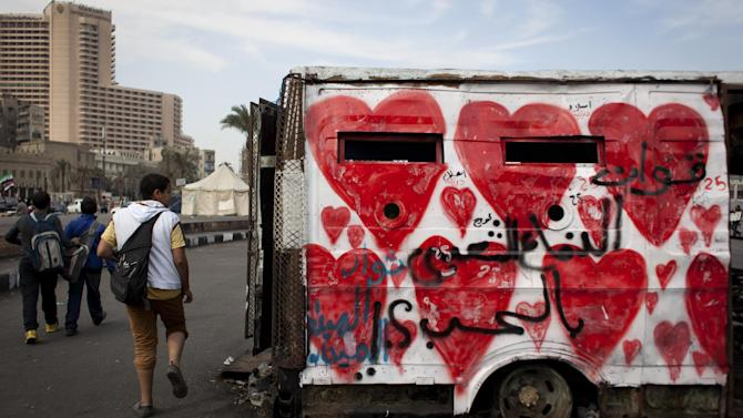 "Egyptian youths walk past a captured and burned police armored vehicle by demonstrators in the recent events, that is painted with red hearts and Arabic that reads ""the love popular defense forces,"" in Tahrir Square, Cairo, Egypt, Tuesday, Feb. 19, 2013. An ultraconservative Islamist adviser to Egypt's president resigned Monday in solidarity with a fellow aide who was fired amid allegations of abuse of office. (AP Photo/Nasser Nasser)"