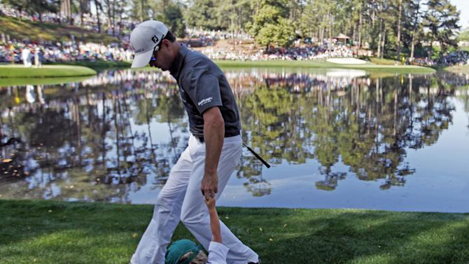 Zach Johnson tries to lift his son after he tripped while walking between holes during the par three competition before the Masters golf tournament Wednesday, April 10, 2013, in Augusta, Ga. (AP Photo/David Goldman)