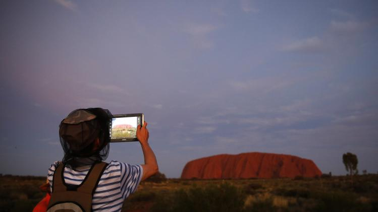 A tourist uses his mobile device to take pictures of the setting sun at Ularu