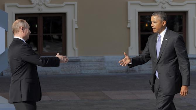 Russia's President Vladimir Putin, left, reaches out to shake hands with U.S. President Barack Obama during arrivals for the G-20 summit at the Konstantin Palace in St. Petersburg, Russia on Thursday, Sept. 5, 2013. The threat of missiles over the Mediterranean is weighing on world leaders meeting on the shores of the Baltic this week, and eclipsing economic battles that usually dominate when the G-20 world economies meet. (AP Photo/Dmitry Lovetsky)
