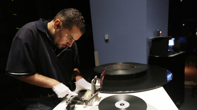 "In this July 16, 2012 photo, Joe Colombo works on splicing together reels of film for the upcoming showing of the latest Batman film, ""The Dark Knight Rises,"" at the IMAX theater at Liberty Science Center in Jersey City, N.J. The museum will have its first ever showing of a feature film shown on the same day it premiers at commercial theaters at midnight on Friday morning. Director Christopher Nolan shot nearly half of his Batman finale using bulky IMAX cameras, whose 70mm frame is about 10 times the size of standard movie film. He also insisted that distributor Warner Bros. release ""The Dark Knight Rises"" in at least 100 IMAX cinemas that can project it on film rather than in the digital format that has been gradually replacing celluloid.(AP Photo/Julio Cortez)"