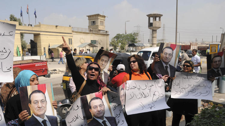 "FILE - In this Saturday, Oct. 6, 2012 file photo, Egyptian women holding pictures of ousted President Hosni Mubarak chant slogans in front of Tora prison, where Mubarak is serving a life sentence, during a show of solidarity on the 6th of October national holiday marking the 1973 war with Israel, in Cairo, Egypt. The signs in Arabic read, ""you cowardly brother,"" and ""the history of our hero will not be forgotten."" Mubarak served as the commander of the country's air force during the war. It was one of the most perplexing events of Egypt's 2011 revolution: Attacks on prisons that broke out more than 20,000 inmates, among them Hamas and Hezbollah militants and Muslim Brotherhood leaders, including the man who is now the country's president, Mohammed Morsi. Now a court case is trying to uncover for the first time who was behind the attacks, raising political headaches for Morsi.  (AP Photo/Mohmmed Asad, File)"