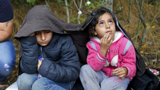 Children of Syrian migrants cover themselves from the rain as they rest on the side of a road after crossing the border illegally from Serbia, near Asotthalom