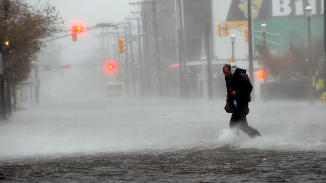 Michael Wirtz, of Wilmington, Del., braves flood waters and high winds that arrive with Hurricane Sandy along North Michigan Avenue in Atlantic City, N.J., Monday Oct. 29, 2012. Hurricane Sandy continued on its path Monday, forcing the shutdown of mass transit, schools and financial markets, sending coastal residents fleeing for higher ground, and threatening a dangerous mix of high winds and soaking rain. (AP Photo/The Press of Atlantic City, Michael Ein) MANDATORY CREDIT