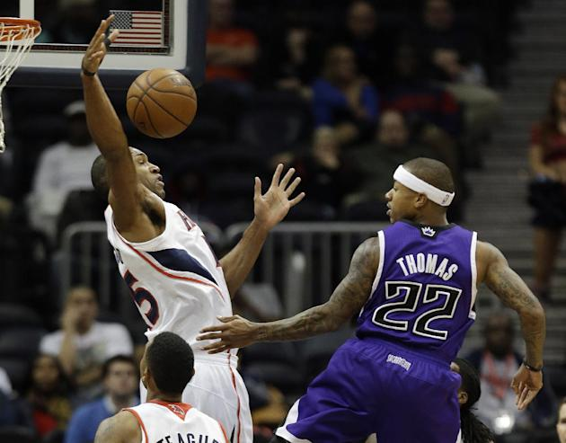Sacramento Kings point guard Isaiah Thomas (22) passes the ball as Atlanta Hawks center Al Horford (15) defends in the first half of an NBA basketball game on Wednesday, Dec. 18, 2013, in Atlanta