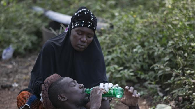Tarawallie holds the head of her husband Ibrahim, 31, a suspected Ebola victim, as they wait to be transported from Devil Hole