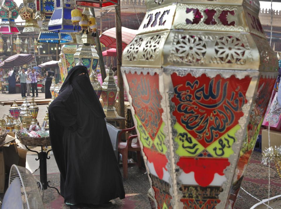 An Egyptian woman buys Ramadan traditional lanterns at a shop ahead of the Muslim fasting month of Ramadan, which begins on Friday, in Cairo, Egypt, Wednesday, July 18, 2012. Throughout the month Muslims must fast from dawn until sunset when they break for the Iftar meal. (AP Photo/Amr Nabil)