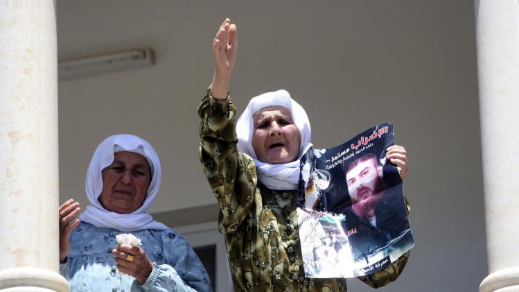 "The mother of Palestinian prisoner Bilal Diab holds a poster of her son, who is on a hunger strike for 67 days, with Arabic that reads, ""the strike will continue..till freedom, glory, and dignity,"" to protest  Israel's military justice system, during a rally in a village near Jenin, West Bank, Friday, May, 4, 2012. A Palestinian rights group said recently that half of about 5,000 Palestinian prisoners held by Israel are on a hunger strike, demanding an end to imprisonment without trial as well as better conditions. (AP Photo/Mohammed Ballas)"