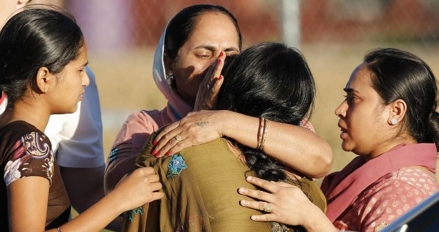 A distraught women is comforted outside of the Sikh temple in Oak Creek, Wisconsin August 5, 2012. A shooting during Sunday services at the temple left at least seven people dead, including a gunman, and at least three critically wounded, police and hospital officials said.     REUTERS/Tom Lynn (UNITED STATES - Tags: CRIME LAW)