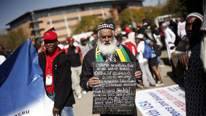 """A man carries a placard calling US President Obama """"The Kitchen Boy of the White House"""" and expressing many things he thinks are wrong with US foreign policy, as Protestors demonstrate against the upcoming visit of U.S. President Barack Obama in Pretoria, South Africa, Friday June 28, 2013. (AP Photo/Jerome Delay)"""