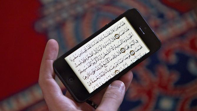A man reads the Koran on an iPhone during a prayer service at the Islamic Society of Boston mosque, Friday, April 26, 2013, in Cambridge, Mass. (AP Photo/Robert F. Bukaty)