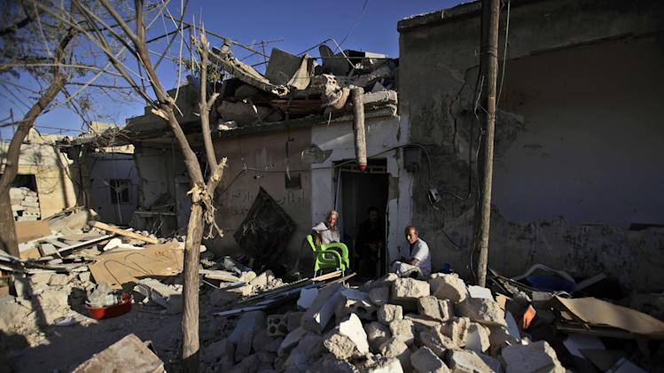Syrian men sit by the doorway of a house destroyed in a Syrian government bombing last week that killed more than 40 people, in Azaz, on the outskirts of Aleppo, Syria, Friday, Aug. 24, 2012. (AP Photo/Muhammed Muheisen)