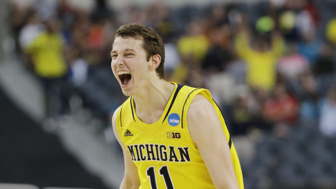 Michigan guard Nik Stauskas reacts after making a 3-point shot against Florida during the first half of a regional final game in the NCAA college basketball tournament, Sunday, March 31, 2013, in Arlington, Texas. (AP Photo/David J. Phillip)