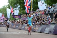 Kazakhstan's Alexandre Vinokourov celebrates as he crosses the finish line to win the Olympic men's cycling road race