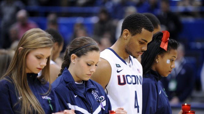 Members of the Connecticut's cheer, dance and basketball teams participate in a service honoring those killed in a school shooting in Newtown, Conn., last Friday. The service was held before an NCAA college basketball game between Connecticut and Maryland Eastern Shore in Hartford, Conn., Monday, Dec. 17, 2012. (AP Photo/Fred Beckham)