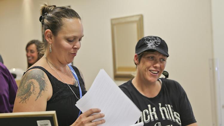 Rose Southall, left, and her partner, Brandi Mahan get the word from Senior Assessment Clerk Jennifer Samuela in the San Diego County marriage license office that ceremonies to get married are booked for the week in San Diego, Monday, July 1, 2013. The couple have been together for 10 and-half-years and said they can wait. (AP Photo/Lenny Ignelzi)