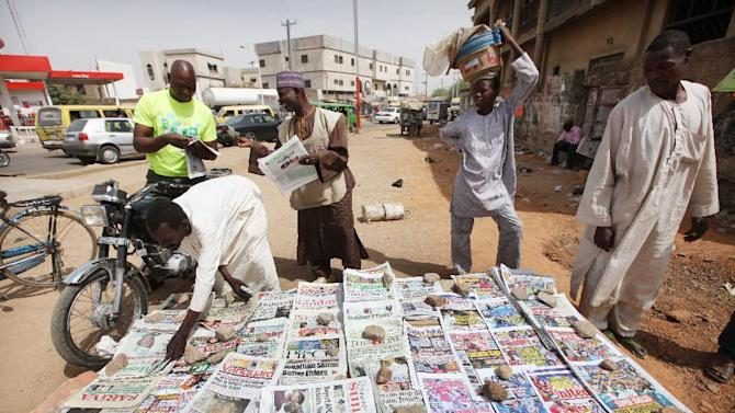 People read local newspapers with headlines like ' We've killed 7 foreign hostages' on a street in Kano, Nigeria, Sunday, March. 10, 2013. The United Kingdom's military says its warplanes recently spotted in Nigeria's capital city were there to move soldiers to aid the French intervention in Mali,not to rescue kidnapped foreign hostages. The Ministry of Defense said Sunday that the planes had ferried Nigerian troops and equipment to Bamako, Mali. An Islamic extremist group in Nigeria called Ansaru partially blamed the presence of those planes as an excuse for claiming Saturday that it killed seven foreign hostages it had taken. ( AP Photo/Sunday Alamba)