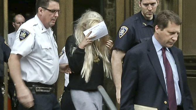 In an image made from video, actress Amanda Bynes, center, wearing sweats and a blonde wig, shields her face as she is escorted after a Manhattan criminal court appearance on Friday May 24, 2013 in New York. Bynes was arrested Thursday evening and charged with reckless endangerment after police say she heaved a marijuana bong out of out of her Manhattan apartment building. (AP Photo/APTN)
