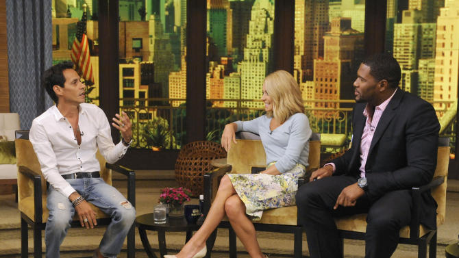"""This image released by Disney-ABC Domestic Television shows Marc Anthony, left, with co-hosts Kelly Ripa, center, and Michael Strahan on """"Live with Kelly and Michael,"""" Thursday, July 18, 2013, in New York. Marc Anthony touted his roots on """"Live with Kelly and Michael"""" on Thursday after some people criticized his selection to sing """"God Bless America"""" at this week's major league baseball All-Star Game, held in New York. The Grammy-winning salsa star said that he heard people were questioning why a foreign-born person was singing the patriotic song. Anthony said he was born in New York and added: """"You can't get more New York than me."""" (AP Photo/Disney-ABC Domestic Television, Jeff Neira)"""