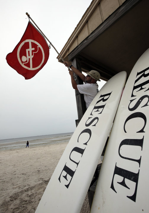 Lifeguard Duane Gonzalez takes down the red warning flag on a beach in Tampa, Fla., Sunday, Aug. 26, 2012.  Some rain and winds from Tropical Storm Isaac are beginning to reach Tampa where the Republi