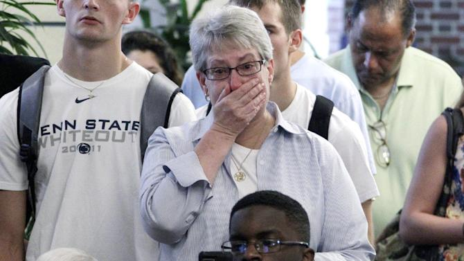 Susan DelPonte, center, of State College, Pa., reacts to a television in the HUB on the Penn State University main campus in State College, Pa., as the NCAA sanctions against the Penn State University football program are announced Monday, July 23, 2012. The NCAA slammed Penn State with an unprecedented series of penalties Monday, July 23, 2012,  including a $60 million fine and the loss of all coach Joe Paterno's victories from 1998-2011, in the wake of the Jerry Sandusky child sex abuse scandal.  (AP Photo/Gene J. Puskar)