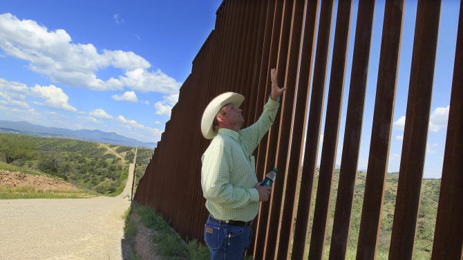 In this Friday, Aug. 10, 2012 photo, rancher Dan Bell checks out part of the property he leases at the border fence between the United States and Mexico, in Nogales, Ariz. When Bell drives through the property, he speaks of the hurdles that the Border Patrol faces in his rolling green hills of oak and mesquite trees: The hours it takes to drive to some places, the wilderness areas that are generally off-limits to motorized vehicles, and the environmental reviews required to extend a dirt road. (AP Photo/Ross D. Franklin)