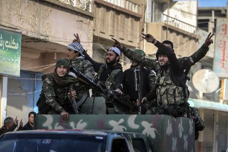 Fighters of the Kurdish People's Protection Units (YPG) carry their weapons along a street in the Syrian Kurdish city of Qamishli, in celebration after it was reported that Kurdish forces took control of the Syrian town of Tel Hamis