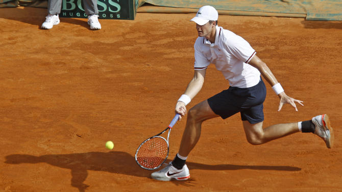 U.S. team player John Isner returns the ball to France's Gilles Simon during their match in the quarterfinal of the Davis Cup between France and U.S. in Monaco Friday April 6, 2012.(AP Photo/Remy de la Mauviniere)